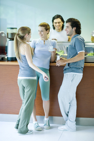 Young adults dressed in exercise clothes, standing by snack bar, chatting