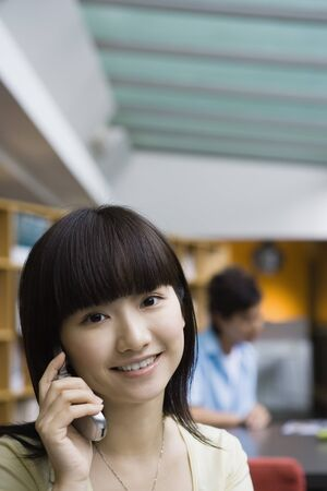 Young woman using cell phone LANG_EVOIMAGES