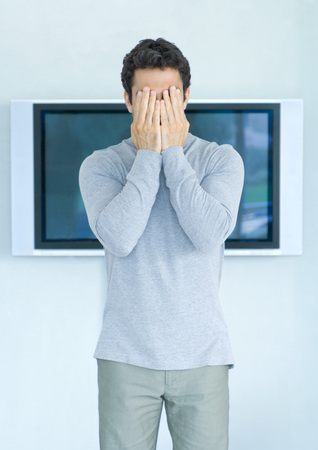 Man standing in front of wide screen TV, hands covering face LANG_EVOIMAGES
