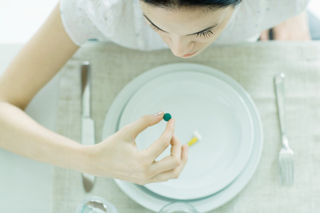 levantar peso: Mujer sentada en un plato vacío con vitamina