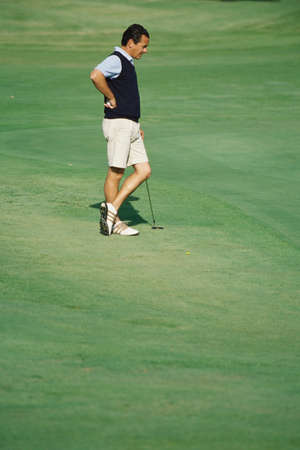 Golfer standing on green, hand on hip and ankles crossed