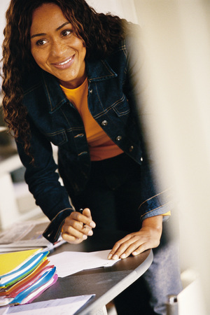 distractions: Young woman leaning over writing on edge of desk