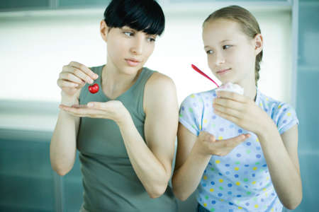 Girl holding ice cream dessert, next to woman holding cherry LANG_EVOIMAGES