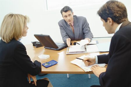 persuading: Professional couple sitting in meeting with sales executive