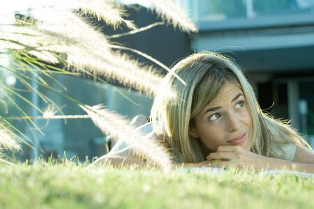 Woman lying in grass, with book, looking up