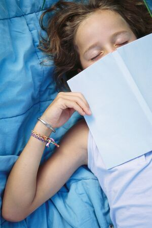 Girl sleeping with book over face LANG_EVOIMAGES