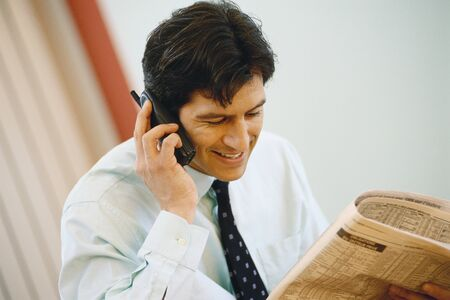 Businessman using phone and holding up financial section of newspaper