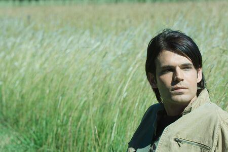 Man sitting in long grass, looking away