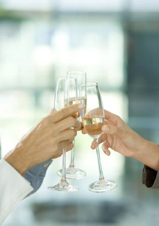 Toasting with glasses of champagne, cropped view of hands