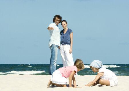 arrodillarse: Familia en la playa, los padres que miran a las hijas juegan en arena LANG_EVOIMAGES