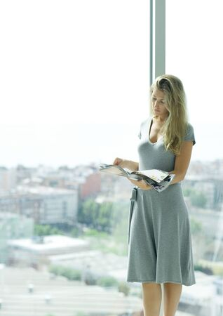Young woman standing by window, looking at magazine
