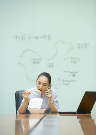 burned out: Businesswoman sitting at desk eating takeout food and using cell phone
