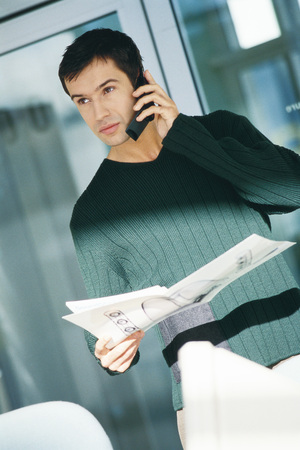 Young male office worker holding document, using telephone LANG_EVOIMAGES
