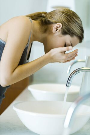 Woman washing face over sink, side view