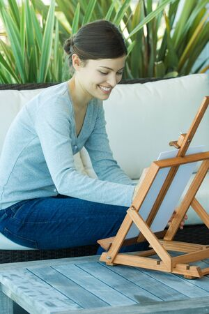 easel: Young woman painting with easel LANG_EVOIMAGES