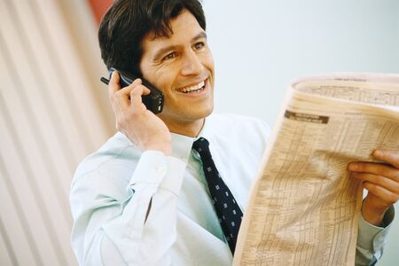 Businessman using phone and holding up financial section of newspaper, smiling