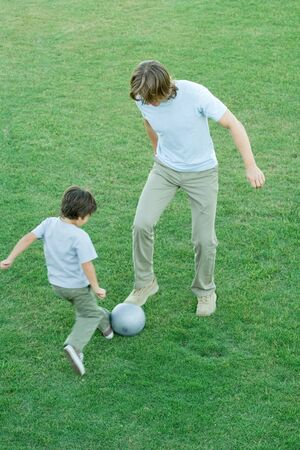 Young man and boy playing soccer on lawn, high angle view