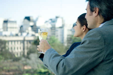 Business partners holding up glasses of champagne, skyline in background LANG_EVOIMAGES
