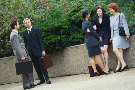 Business executives standing outdoors in groups, chatting