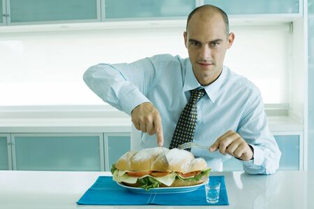 Man cutting into large sandwich with knife and fork