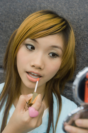 beauties: Young woman putting on lip gloss LANG_EVOIMAGES