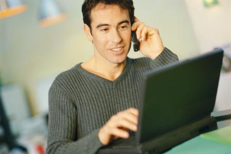 Man using laptop, speaking on cell phone