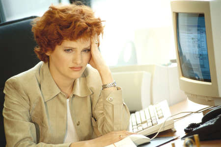 Businesswoman sitting at desk, holding head