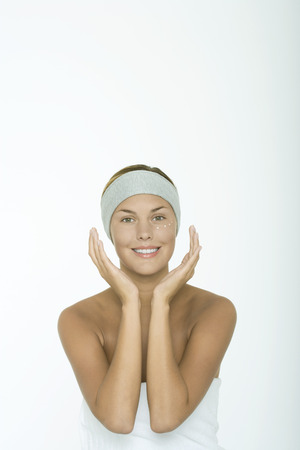 Young woman with dots of moisturizer under eye, hands around face