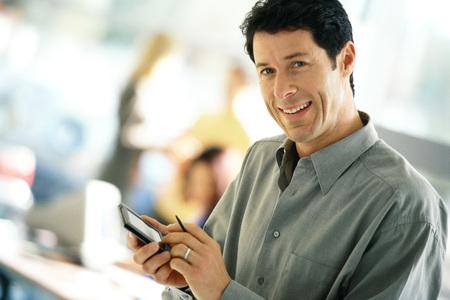 Man using electronic organizer, smiling at camera LANG_EVOIMAGES
