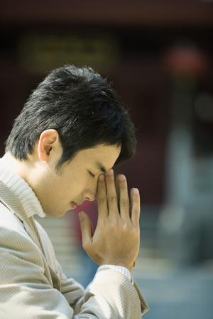 Young man praying LANG_EVOIMAGES