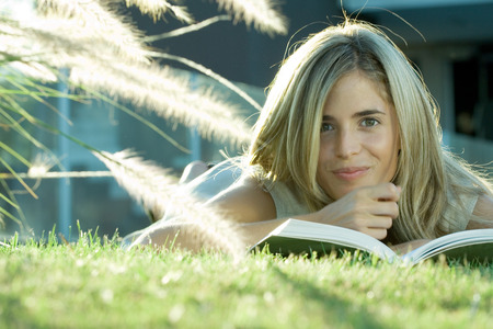 Woman lying in grass, reading book, smiling at camera LANG_EVOIMAGES