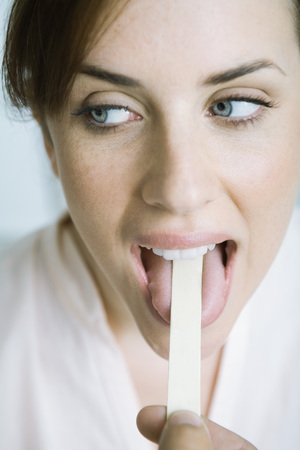 depressor: Woman having tongue held down with tongue depressor LANG_EVOIMAGES
