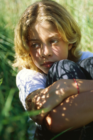 Girl sitting in shade, holding knees, close-up LANG_EVOIMAGES