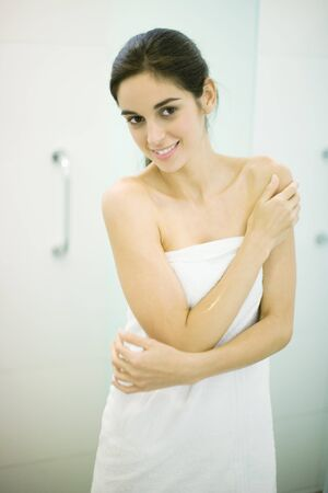 Woman standing wrapped in towel, hand on shoulder, looking at camera LANG_EVOIMAGES