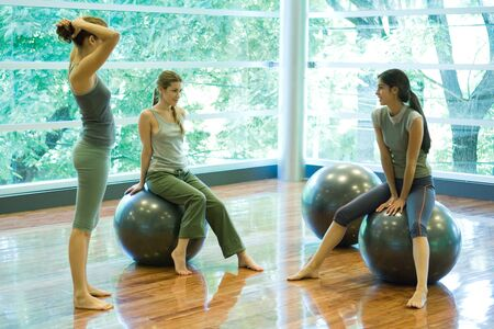 Young women sitting on fitness balls, chatting