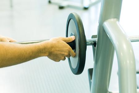 levantar peso: Man adjusting weight on barbell LANG_EVOIMAGES