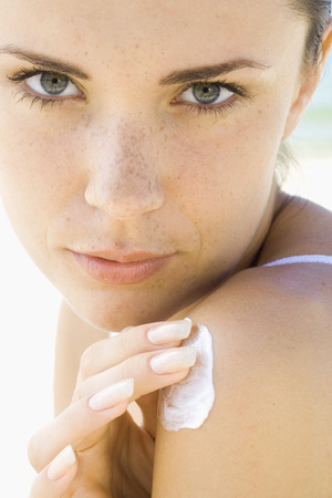 Young woman applying sunscreen to shoulder