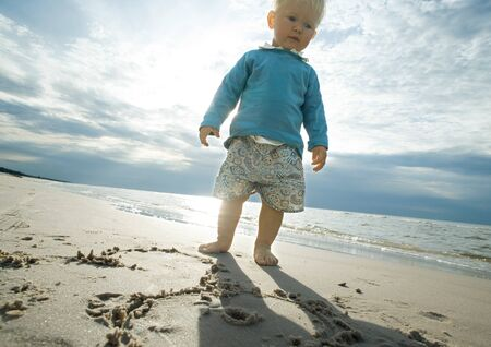 Toddler standing on beach, low angle view