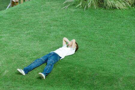 Junge, der auf dem Gras, bedeckendes Gesicht mit den Armen, in voller Länge liegt