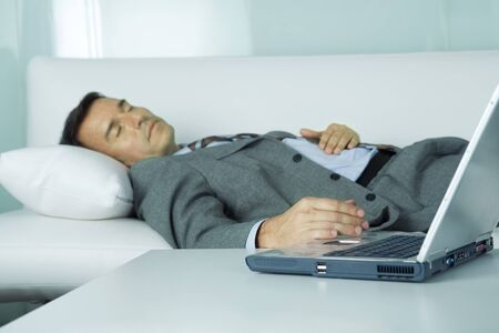 burned out: Businessman sleeping on sofa, hand resting on laptop