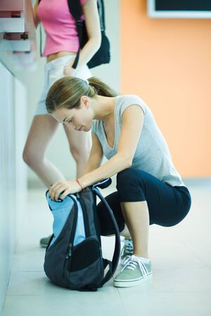 Young woman at health club counter, crouching and looking in backpack