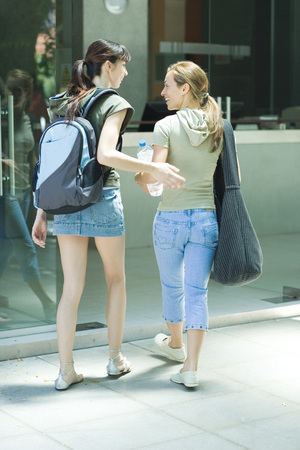 Two young women walking into health club entrance together