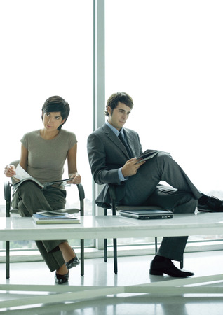 Two young professional adults sitting in waiting room LANG_EVOIMAGES
