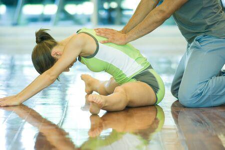 arrodillarse: Instructor de ejercicio que ayuda a la mujer