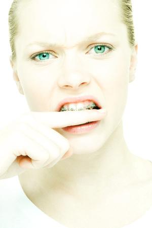 Teenage girl biting finger, close-up LANG_EVOIMAGES