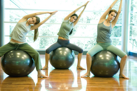Young women sitting on fitness balls, doing side stretch