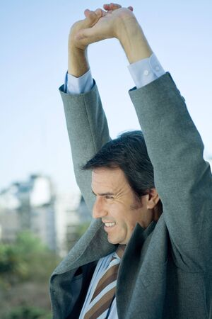 Businessman stretching arms over head