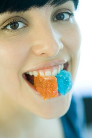 Woman holding pieces of candy between teeth, smiling at camera LANG_EVOIMAGES