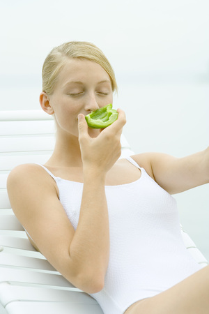 beauties: Teenage girl wearing bathing suit, sitting in lounge chair, smelling piece of green pepper