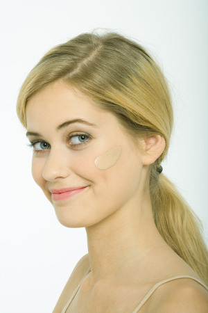 Teenage girl with dollop of foundation on cheek, smiling at camera